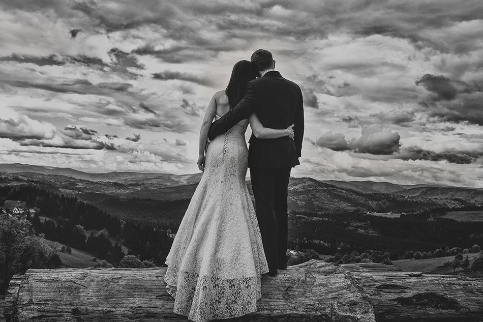 para młoda soi przytulona do siebie i patrzy na doliny i lasy, na niebie rozciągają się burzowe chmury