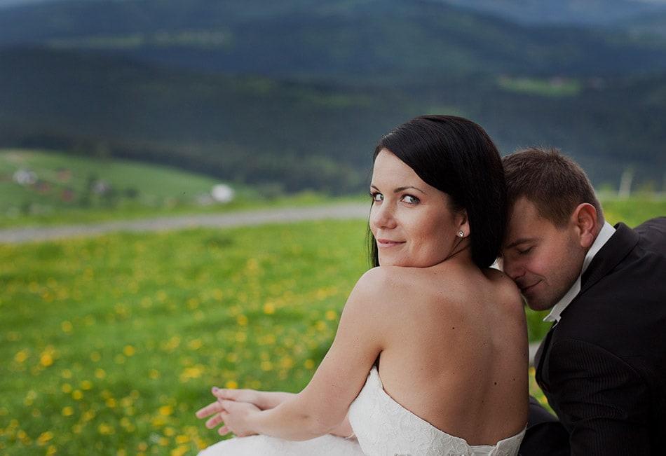 kobieta patrzy do obiektywu, mężczyzna całuje ja w ramie, w tle łąka i góry