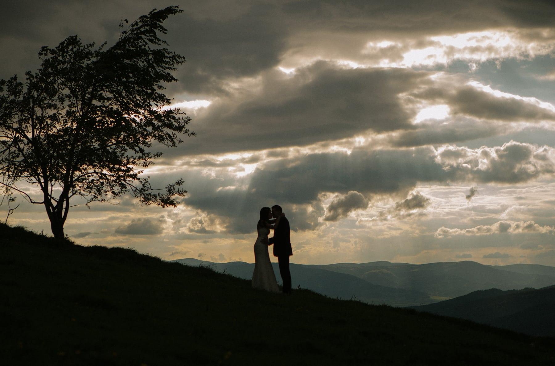 kobieta i mężczyzna stoją naprzeciwko siebie w górach beskidach, otaczająich chmury