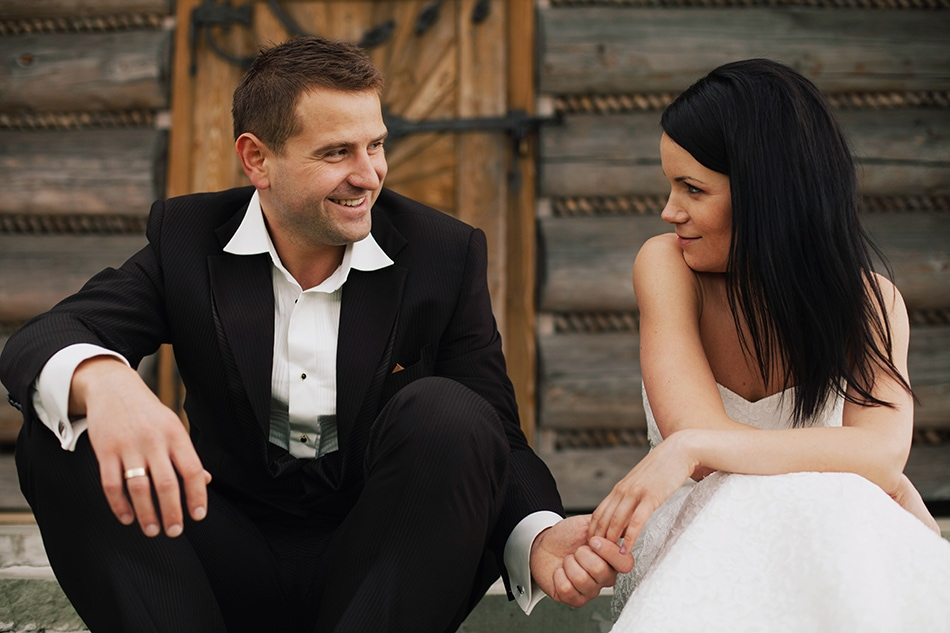 para młoda siedzi przed chatką na ochodzitej, ona patrzym na niego uwodzicielsko, on uśmiecha się wesoło
