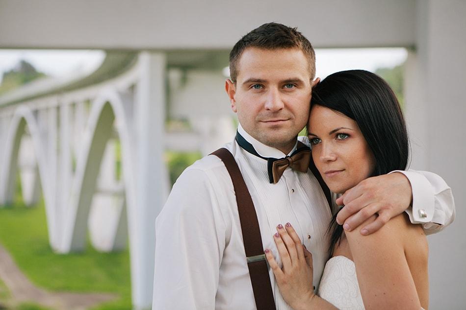 mężczyzna patrzy w obiektyw, kobieta przytula się do jego klatki piersiowej, w tle jest wielki most drogowy