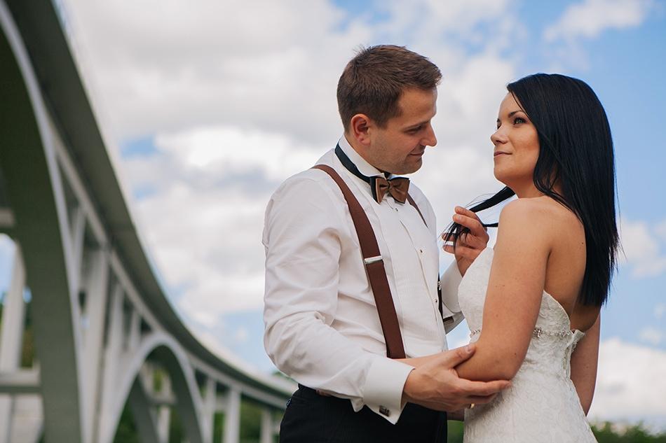 para młoda stoi naprzeciwko siebie, on gładzi włosy żony, w tle jest most