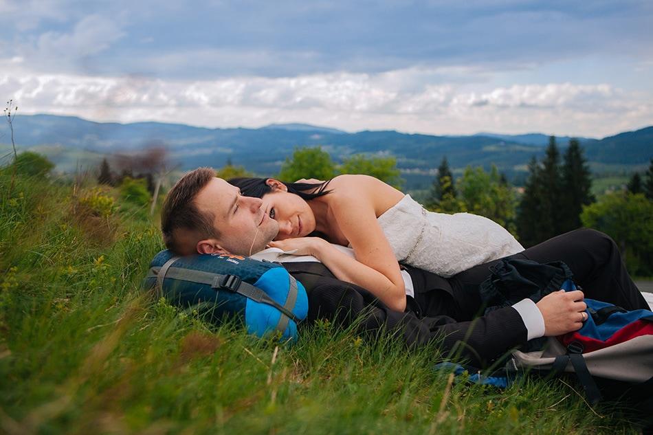 para młoda leży na trawie w górach beskidach, kobieta przytula się do męża i patrzy w obiektyw