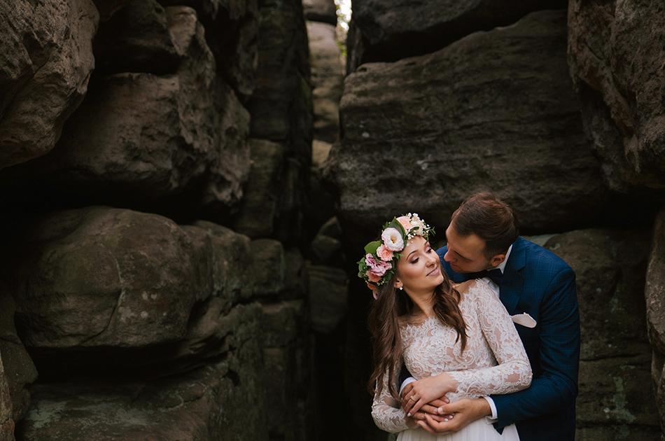 para młoda obejmuje się patrząd na siebie, ona sie uśmiecha, wokół nich znajdują sie skały