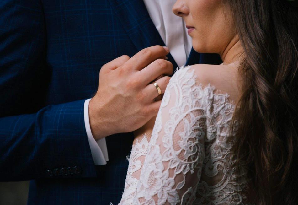 Dziewczyna przytula się do mężczyzny, na jego ręce błyszczy obrączka