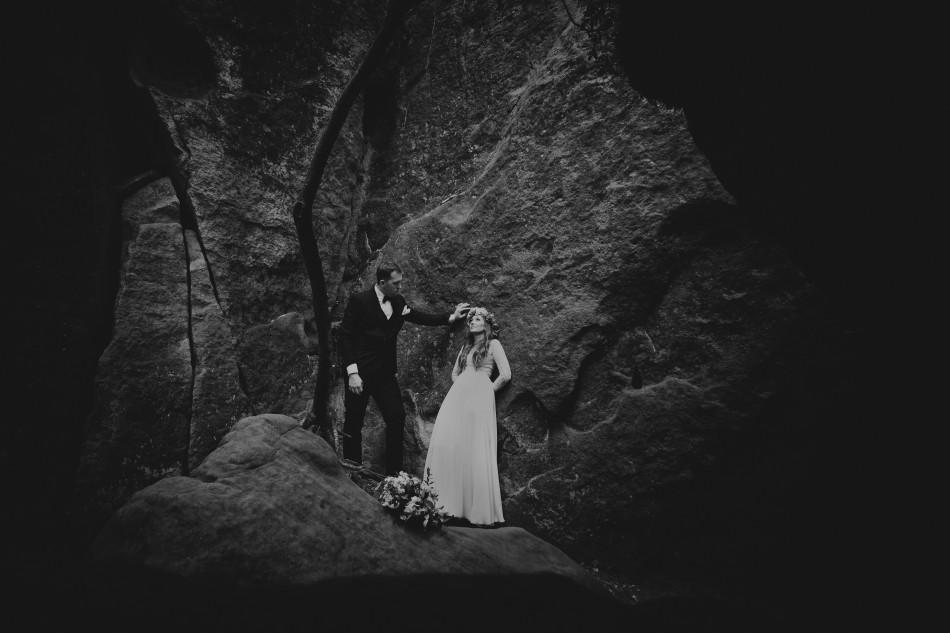 kobieta i mężczyzna są otoczeni skałami, ona opiera się o jedną z nich, on stoi obok