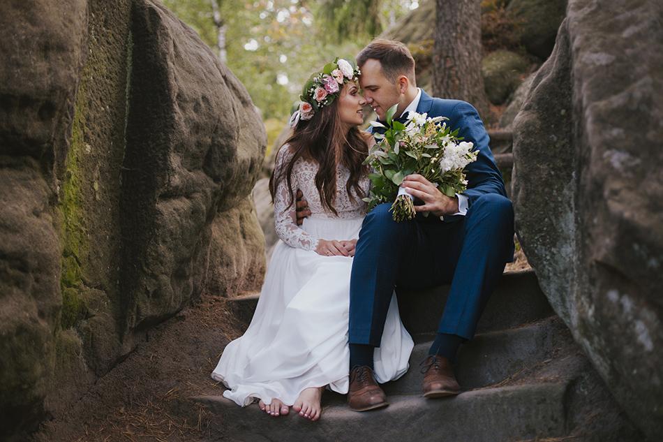 kobiet ai mężczyzna siedza na półkach skalnych w górach stołowych, ich twarze są blisko siebie, on trzyma bukiet ślubny