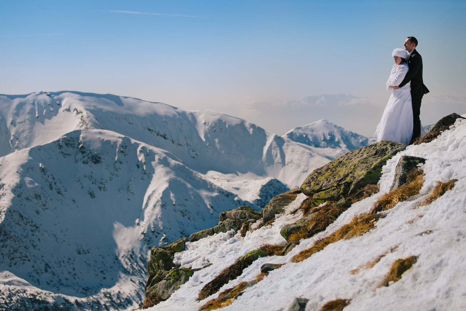 Młoda Para stoi przytulona mrożną zimą na szczycie Kasprowego Wierchu