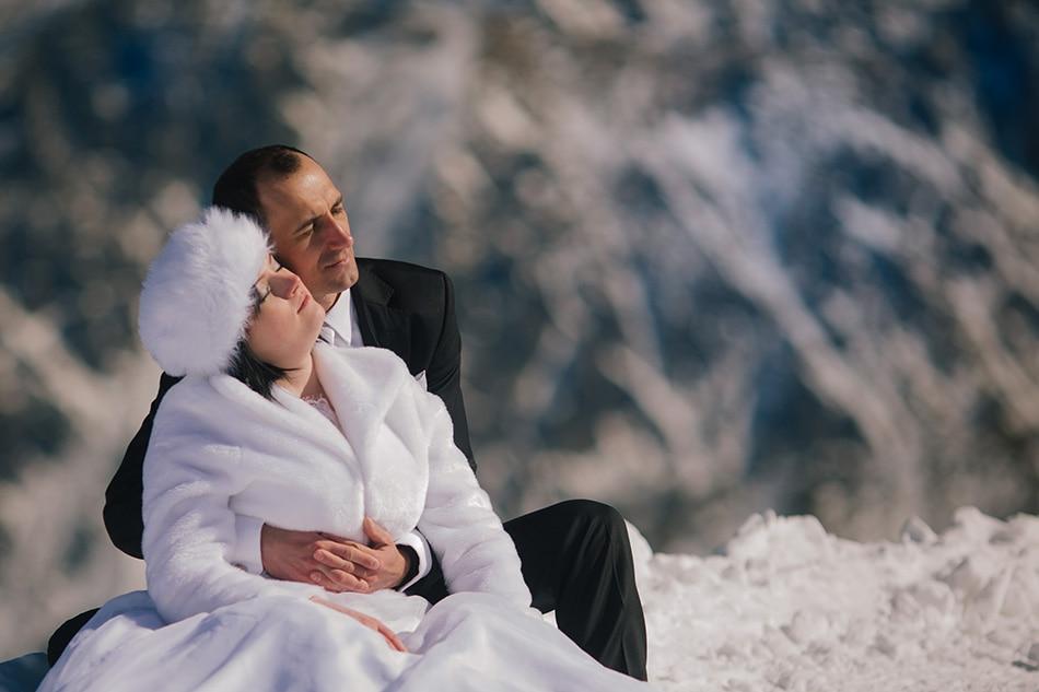 Para Młoda siedzi na śniegu i przytula się do siebie, w tle Góry Tatry