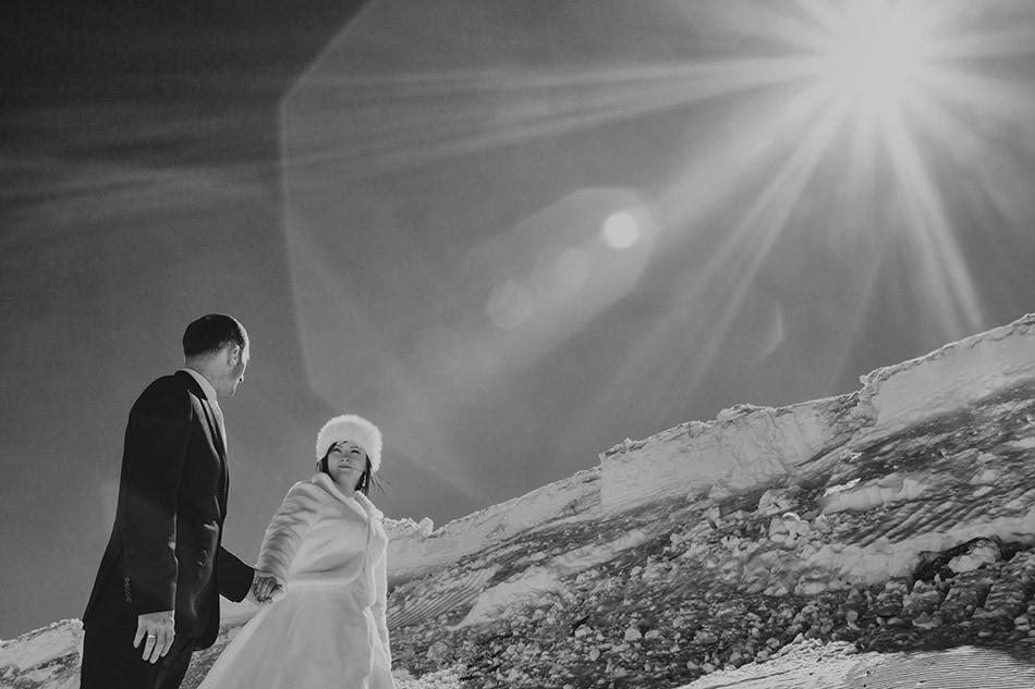 Zakochani spacerują zimą w górach, padają na nich promienie słońca
