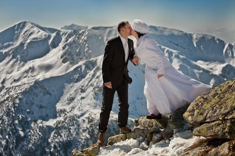 Para Młoda całuję się na skałach, w tle widać panoramę ośnieżonych Tatr