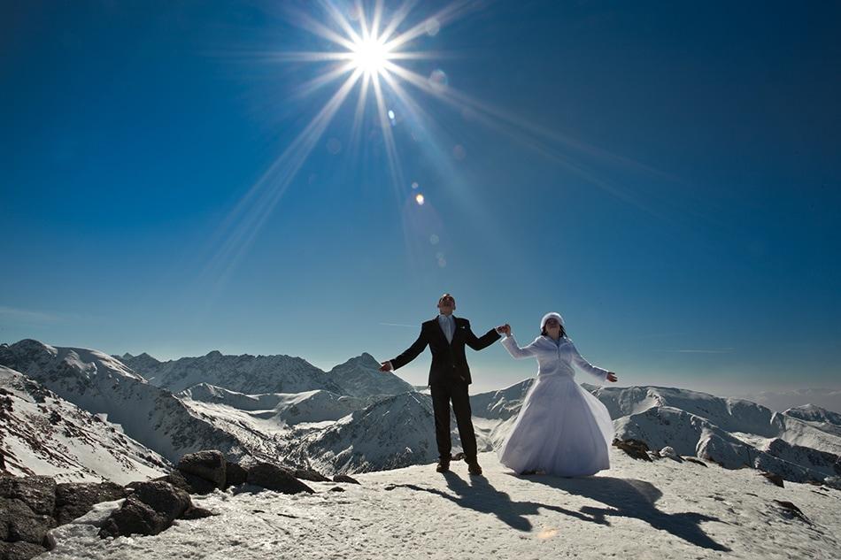 Pan i Pani Młoda trzymią się za ręce w miescu Kasprowy Wierch, w tle widać ośnieżone Tatry, świeci mocne słońce