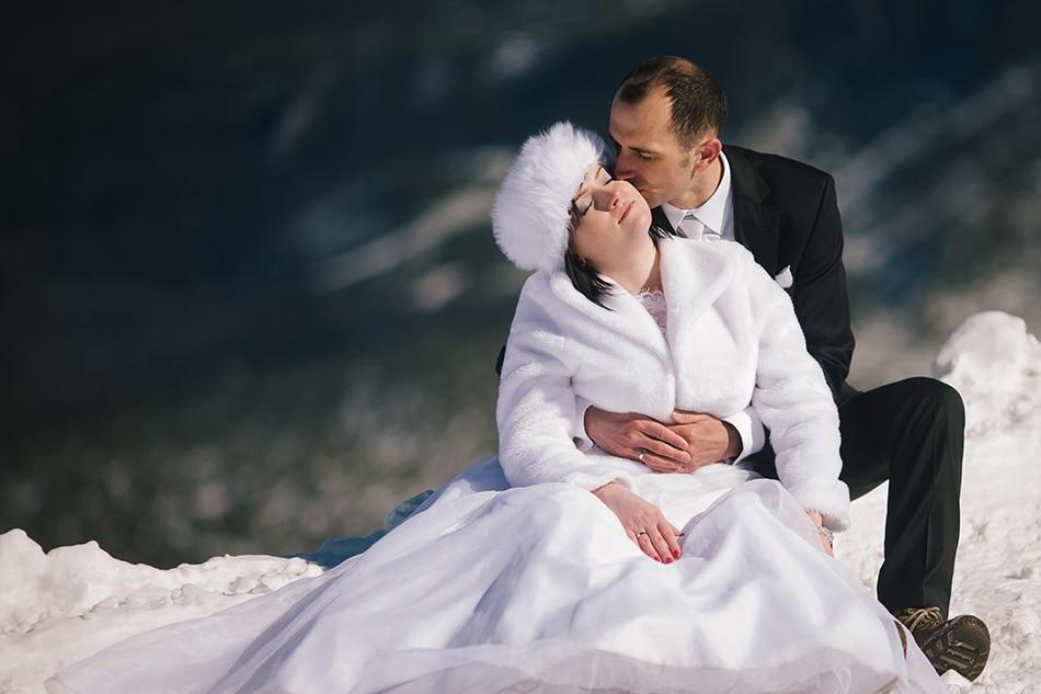 Mężczyzna przyluja i całuje Kobietę w policzek, siedzą oboje na śniegu, w tle widać delikatny zarys Gór Tatr
