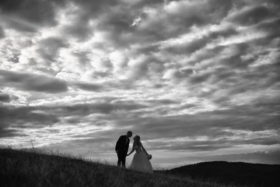 młodzi patrza na siebie i trzymią się za ręce, na niebie zebrało się wiele kontrastowych chmur