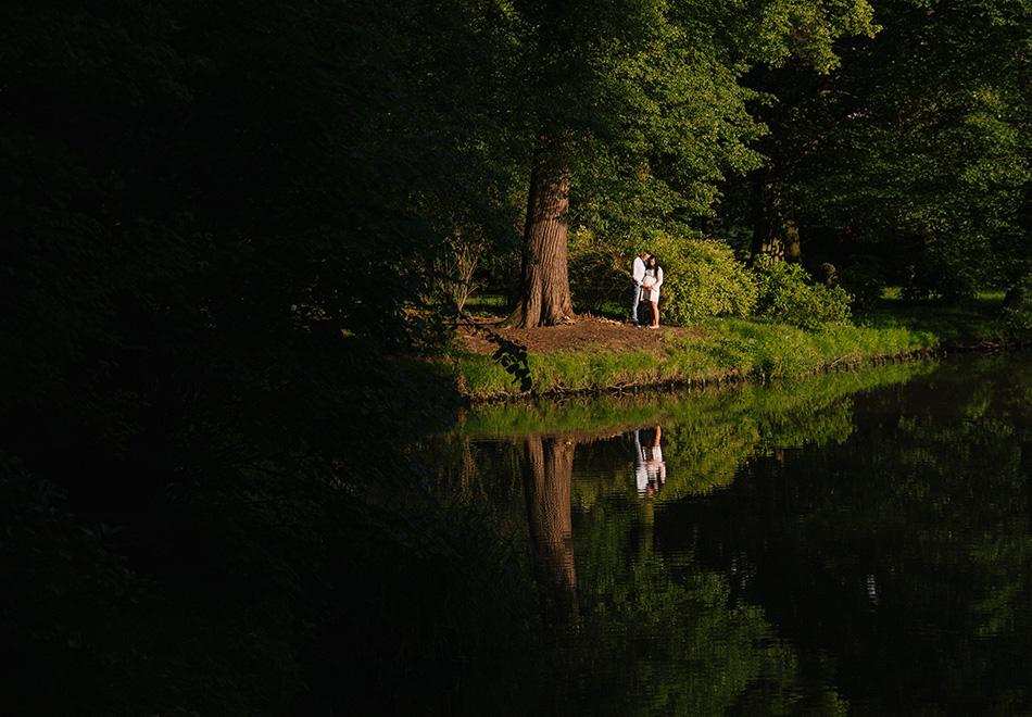 młodzi rodzice oczekujący dziecka, stoją obok siebie w parku pszczyńskim, wokół zielony, piękny las i jezioro