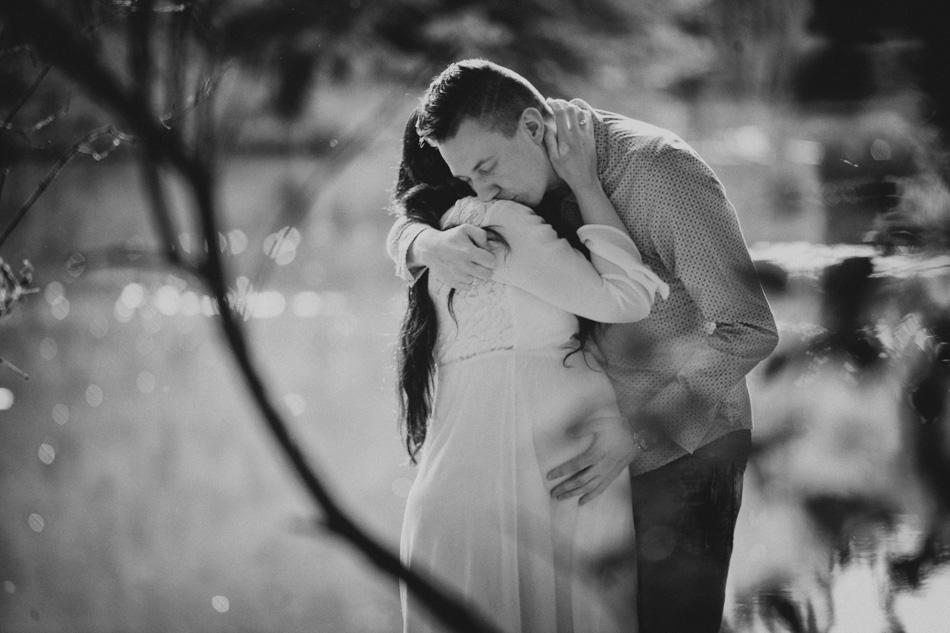 młody mężczyzna przytula się do swojej ciężarnej żony w parku pszczyńskim
