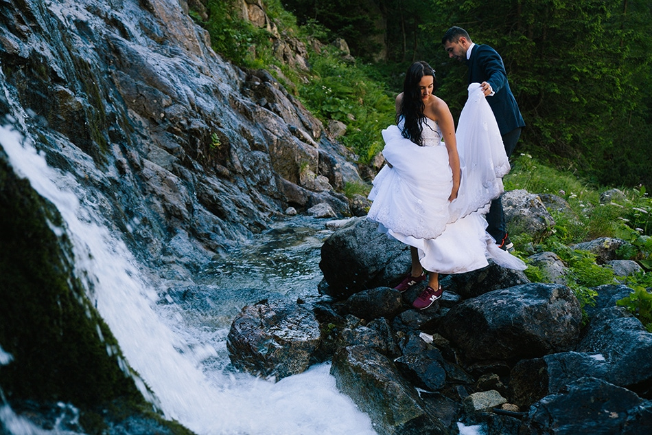 para młoda przechodzi kamienistą ścieżką obok wodospadu