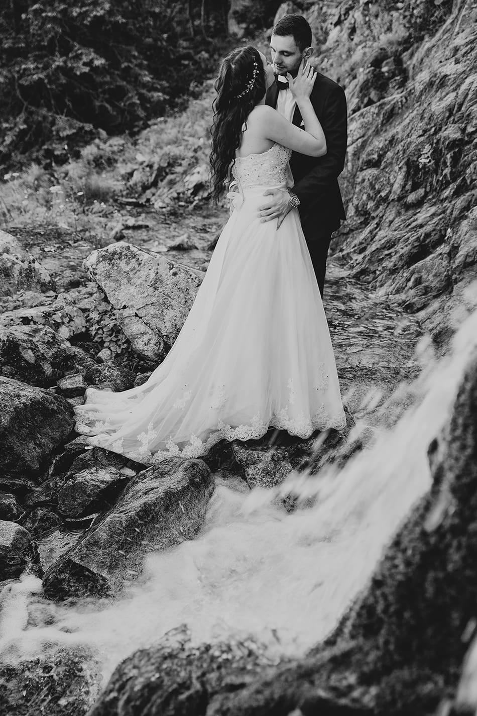Para Młoda przytula stoi w objęciu wpatrzona w siebie nazwajem, przed nimi spływa woda ze skał