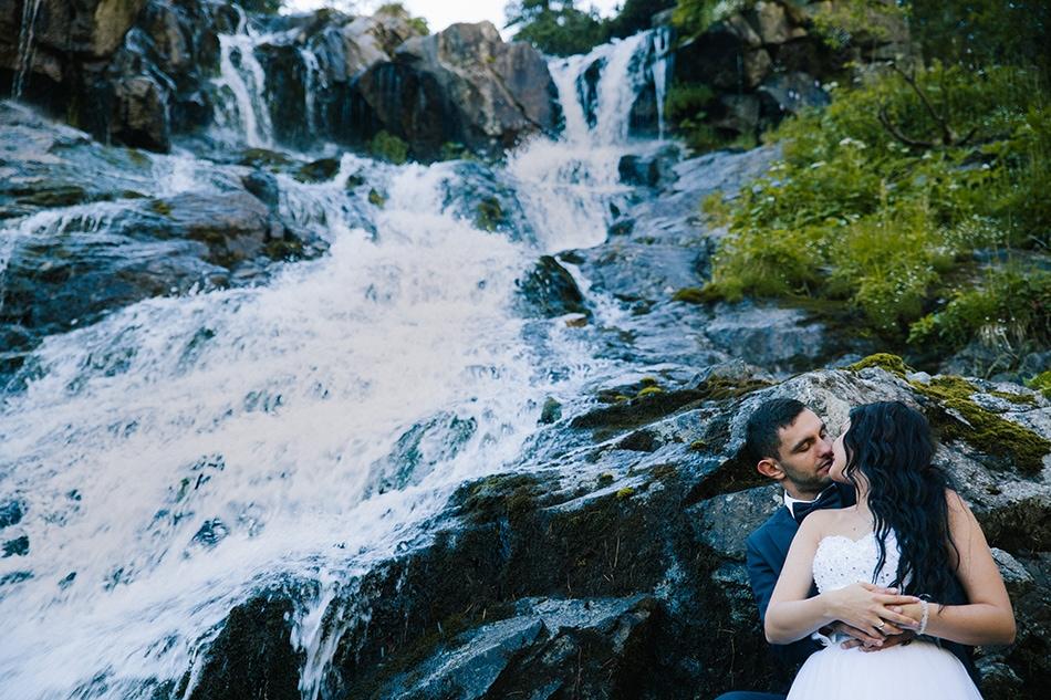 Para Młoda pozuje na tle wodospadu, obok Morskie Oko