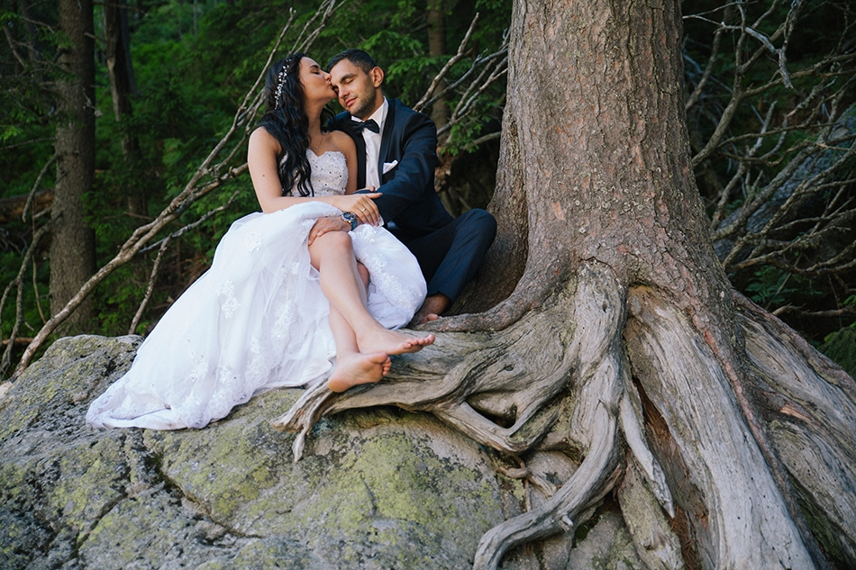 Zdjęcie z okolic Morskiego Oka, Pani Młoda całuje męża, siedzą na skale, obok korzenia olbrzymiego drzewa