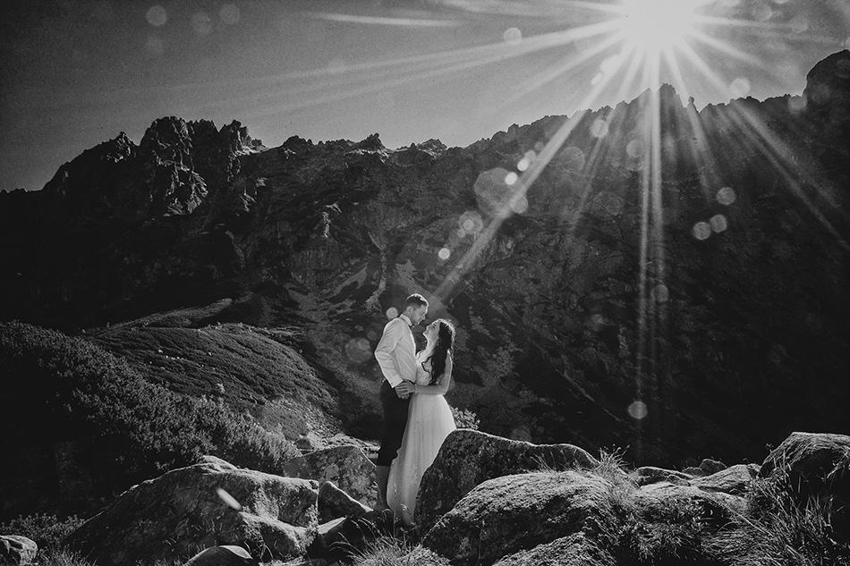 krajobraz Tatr, postaci Pary Zakochanych wpatrujących się w siebie, w tle skały, przebija się słońce