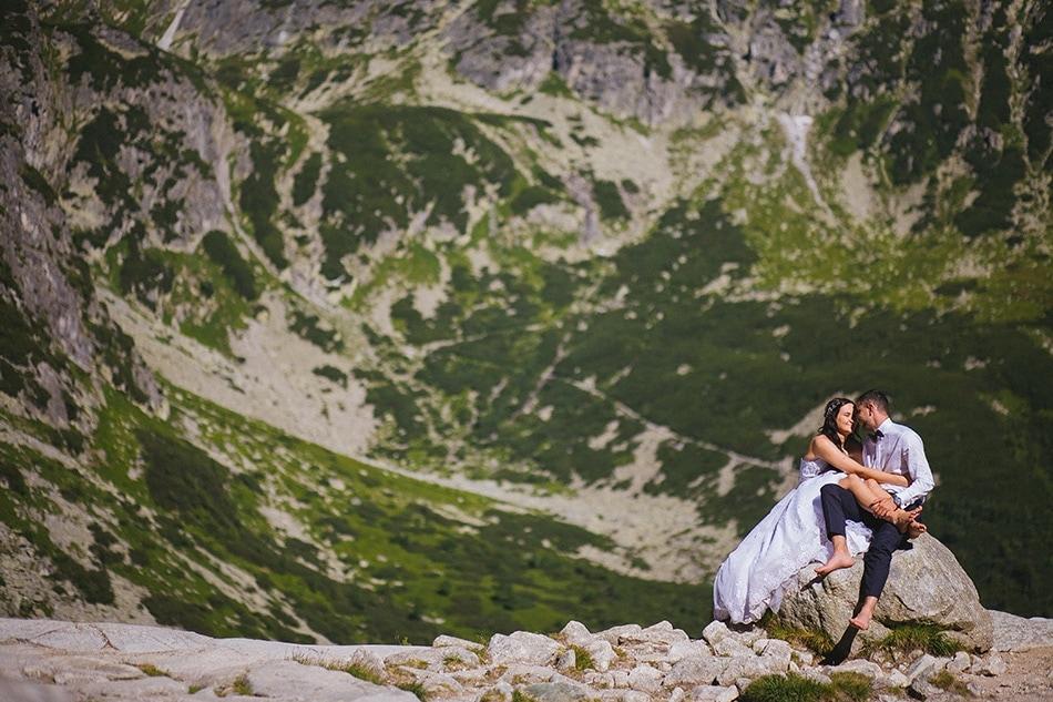 Piękne zdjęcie z Tatr, Para Młoda wiedzi na kamieniu, w tle krajobraz gór