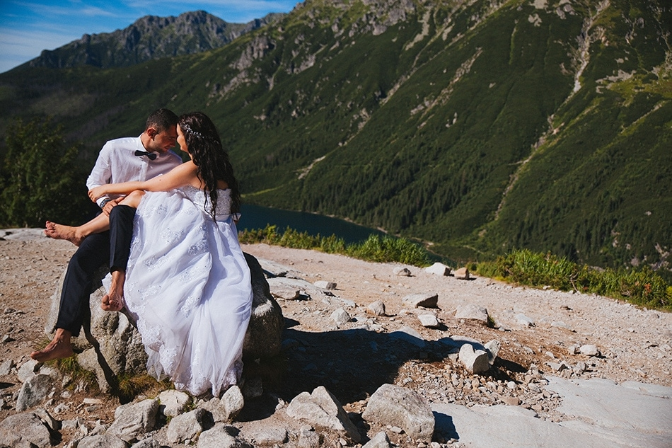 Para siedzi na kamieniu w Tatrach, ich głowy są przytulone