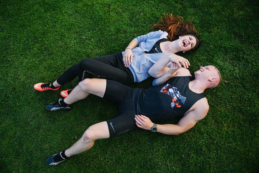 para młodych śmieje się wesoło, leżac na trawie