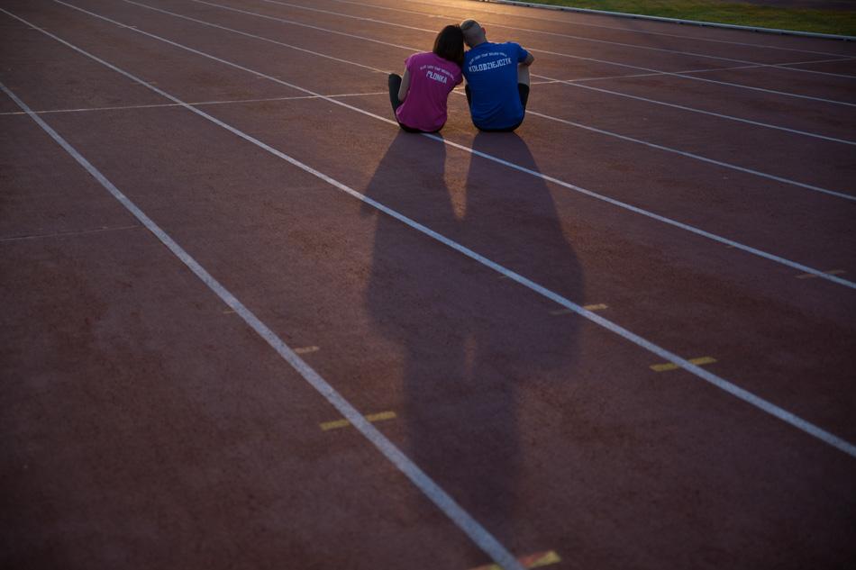 para siedzi na bieźni stadionu, ich głowy łączą się przytulone, za nimi rysuje się wielki cień ich postaci