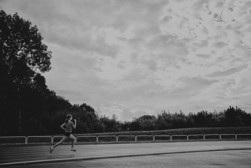 młoda dziewczyna biegnie przez stadion w Wapienicy, jest ubrana w strój sportowy