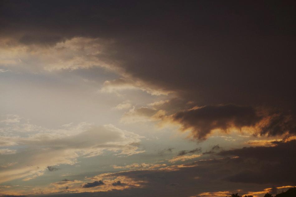 na niebie przez chmury przebijają ostanie promienie słońca
