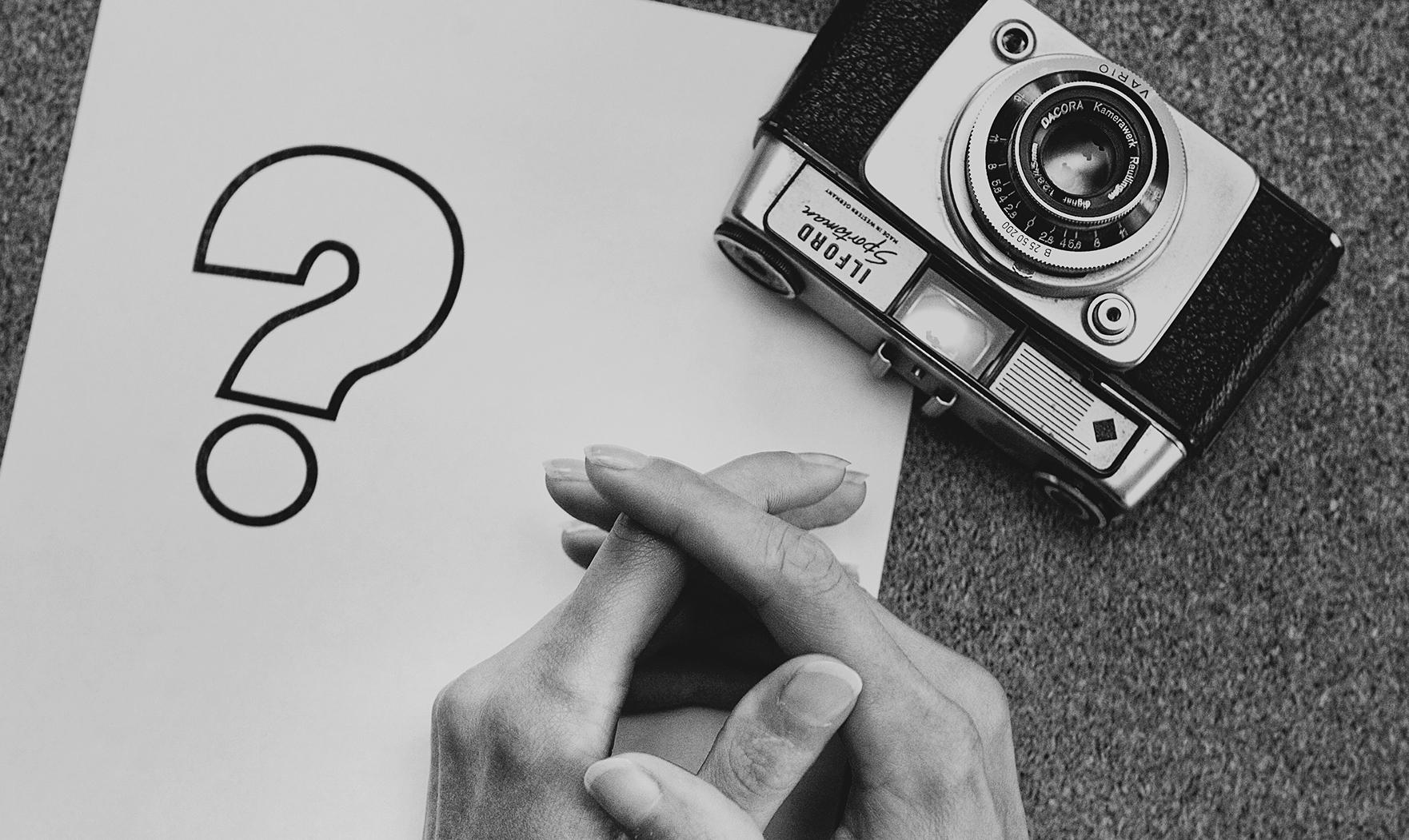 na zdjęciu są dłonie oarate o stół, aparat fotograficzny i symbol znaku zapytania