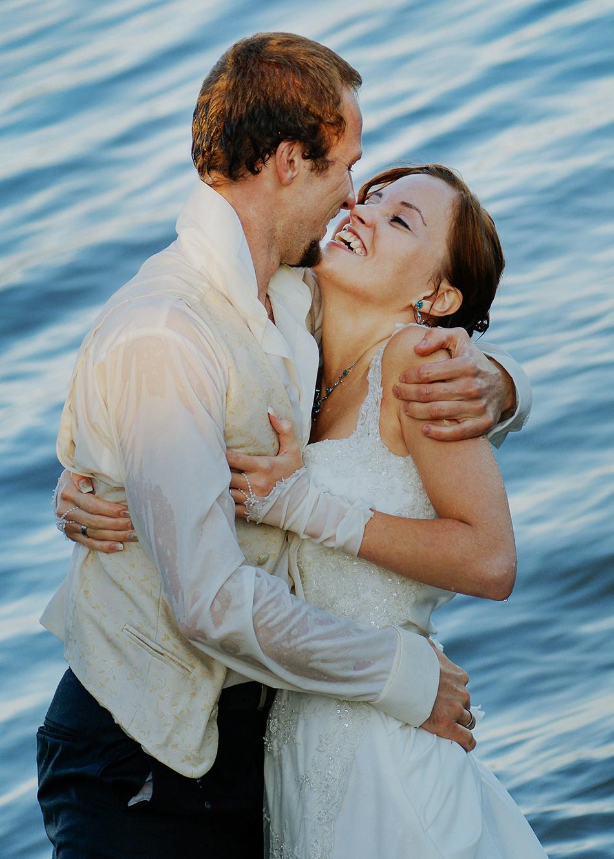 Para Młoda w wodach jeziora żywieckiego, przytulają się i obejmują, ona się śmieje, są mokrzy