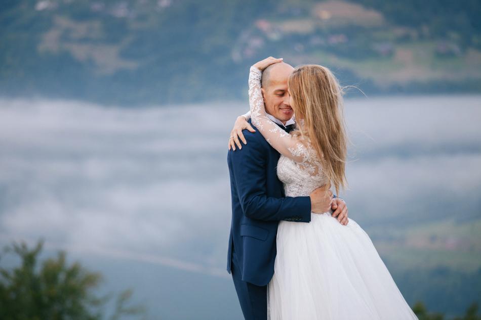 para młoda jest przytulona do siebie, ona głaszcze jego głowę, w tle widać krajobraz i lekką mgłę