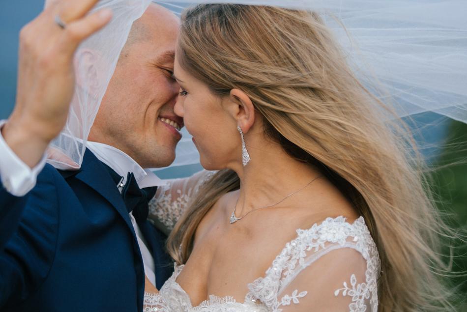 twarze młodych zbliżają się, nad ich głowami powiewa welon ślubny