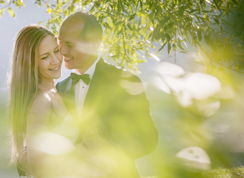 młodzi bardzo radośnie przytulają so siebie twarze, są bardzo radośni, przez liście drzewa przebija się słońce