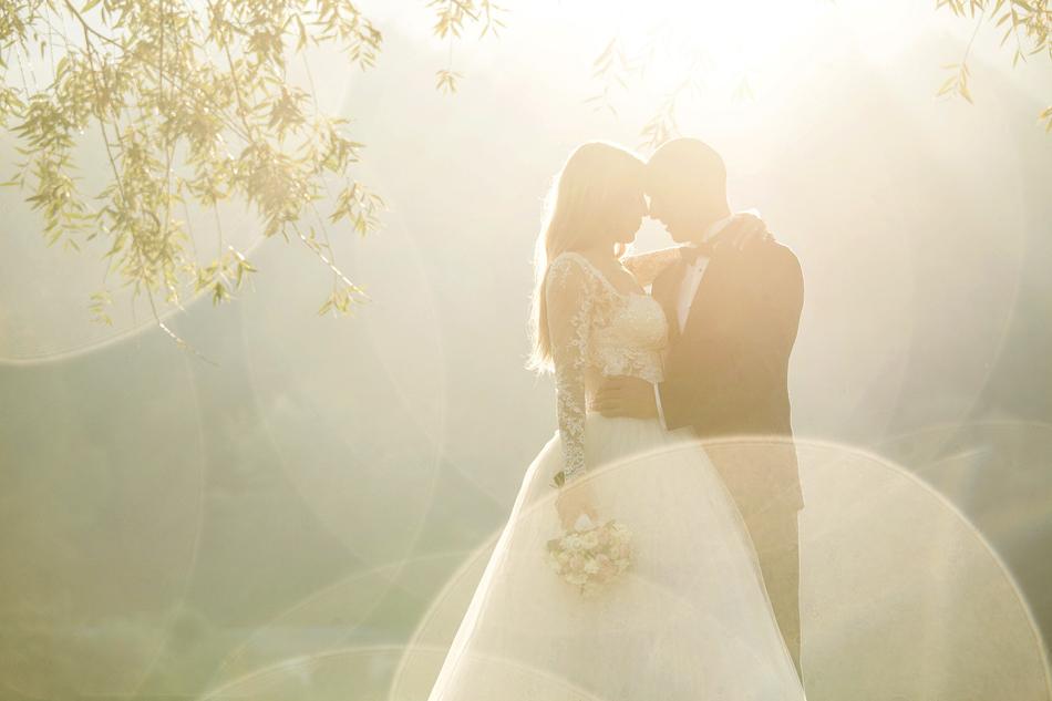 para młoda przytula się do siebie, sa delikatnie oświetleni promieniami wschodzącego słońca