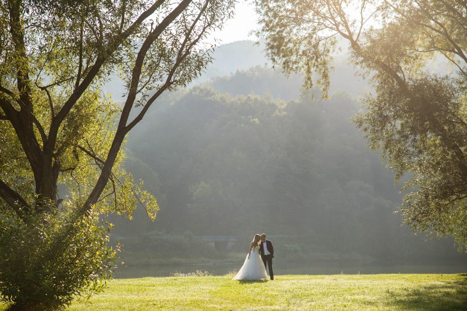 para młoda stoi na łące, ich twarze są blisko siebie, przez drzewa delikatnie padają promienie słońca
