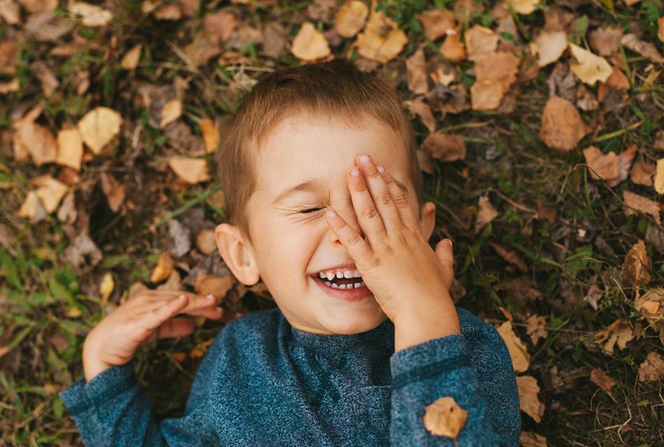 mały chłopczyk leży wśród jesiennych liście i śmieję się wesoło