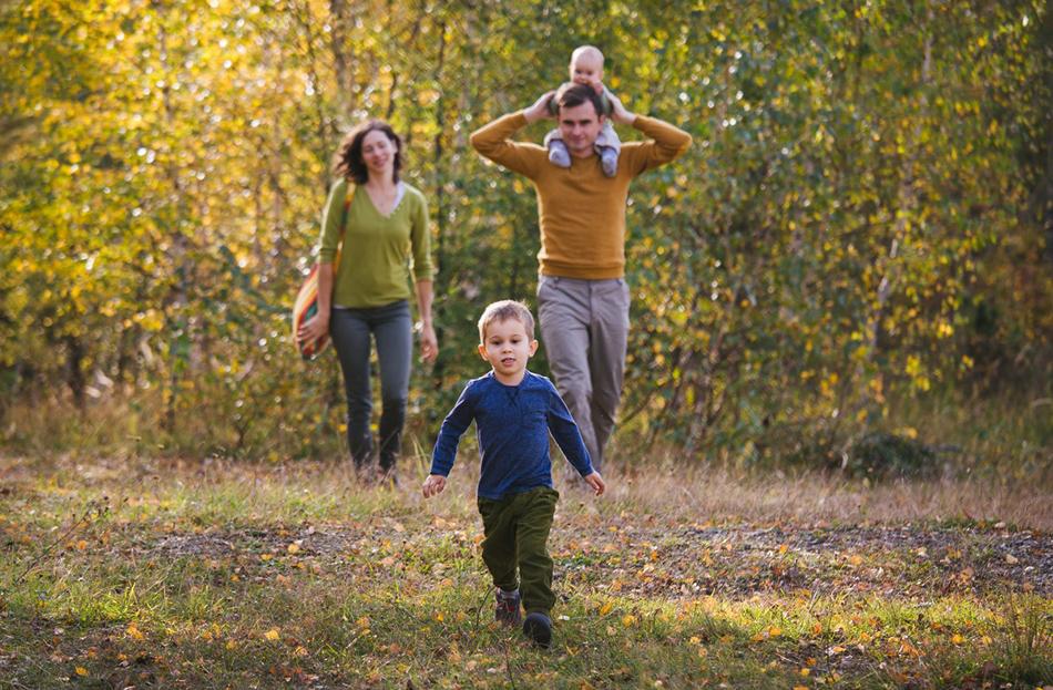 rodzina spaceruje, chłopiec biegnie przed rodzicami, na plecach ojca siedzi mała córeczka