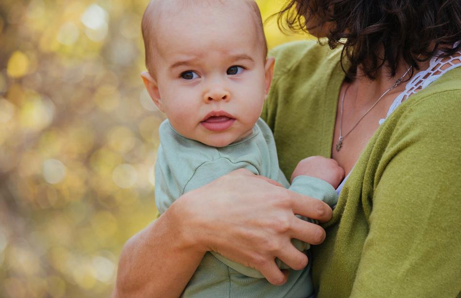 8 miesięczna dziewczynka jest obejmowana przez mamę, w tle widać złotą polską jesień