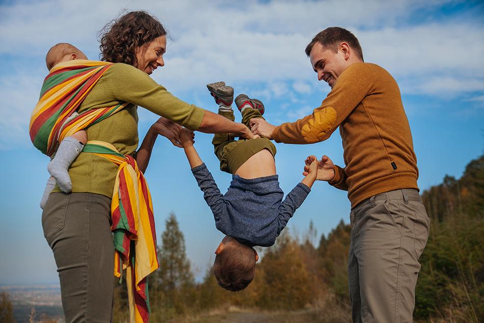 rodzice bawią się z dzieckiem, on na ich rękach robi fikołek