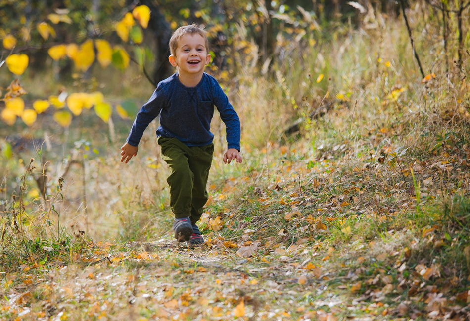 chłopczyk biegnie leśną ścieżką, jest uśmiechnięty