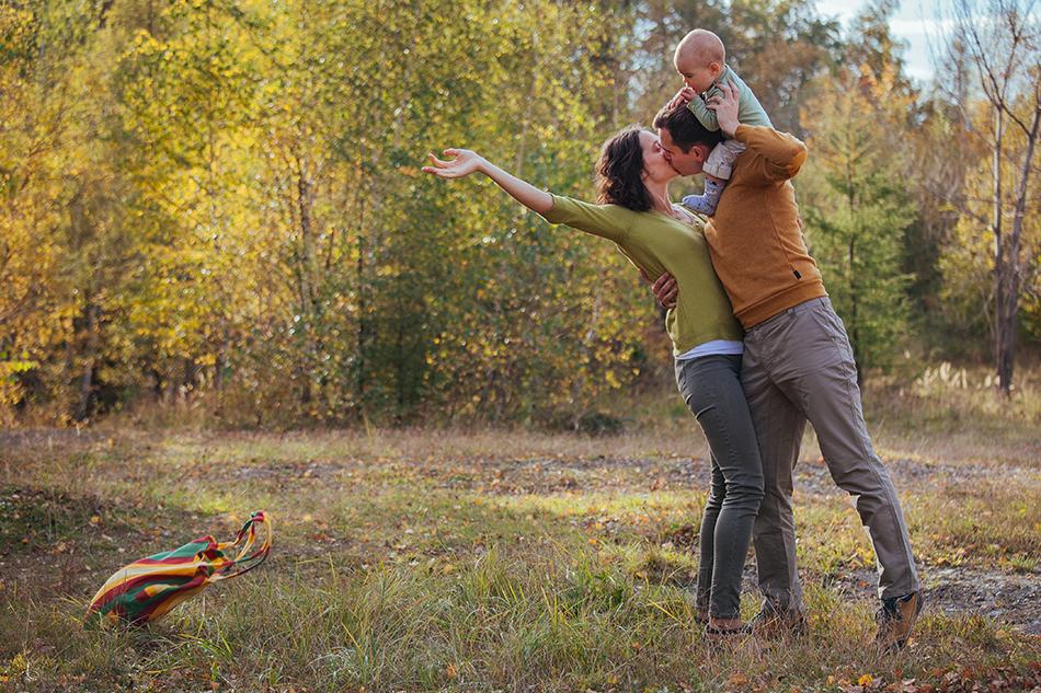na plecach mężczyzny siedzi córeczka, kobieta rzuca torbę za siebie i całuje męża
