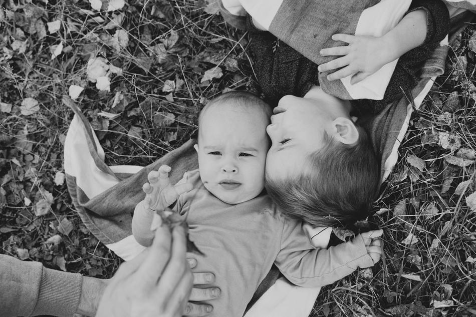 dzieci leżą na liściach, ich głowy łączą się w przytuleniu
