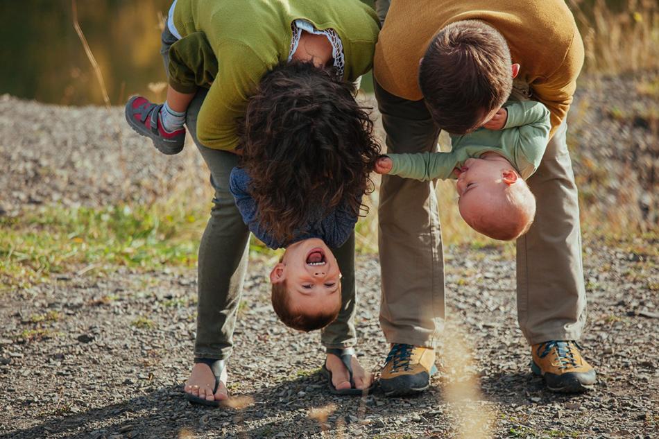 rodzice bawią się za dziećmi, trzymiąc je głowami w dół
