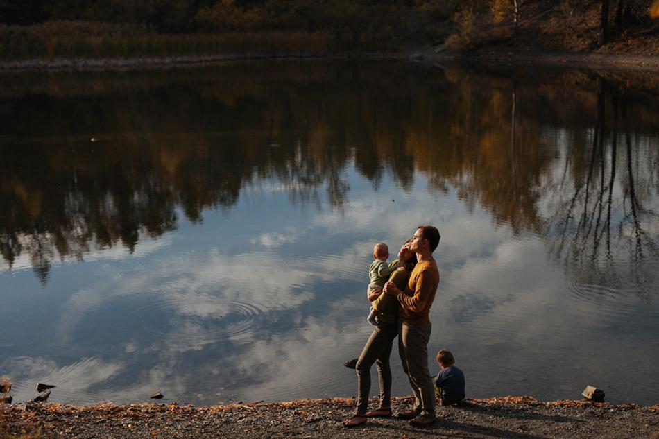 rodzice i dwójka dzieci stoją zwróceni twarzami do słońca, w ich tle w jeziorze odbija się niebo