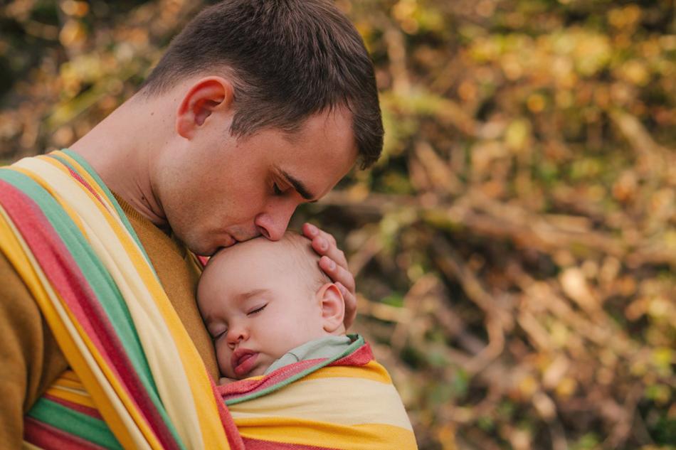 tatuś całuje córeczkę, śpiącą w chuście na jego klatce piersiowej
