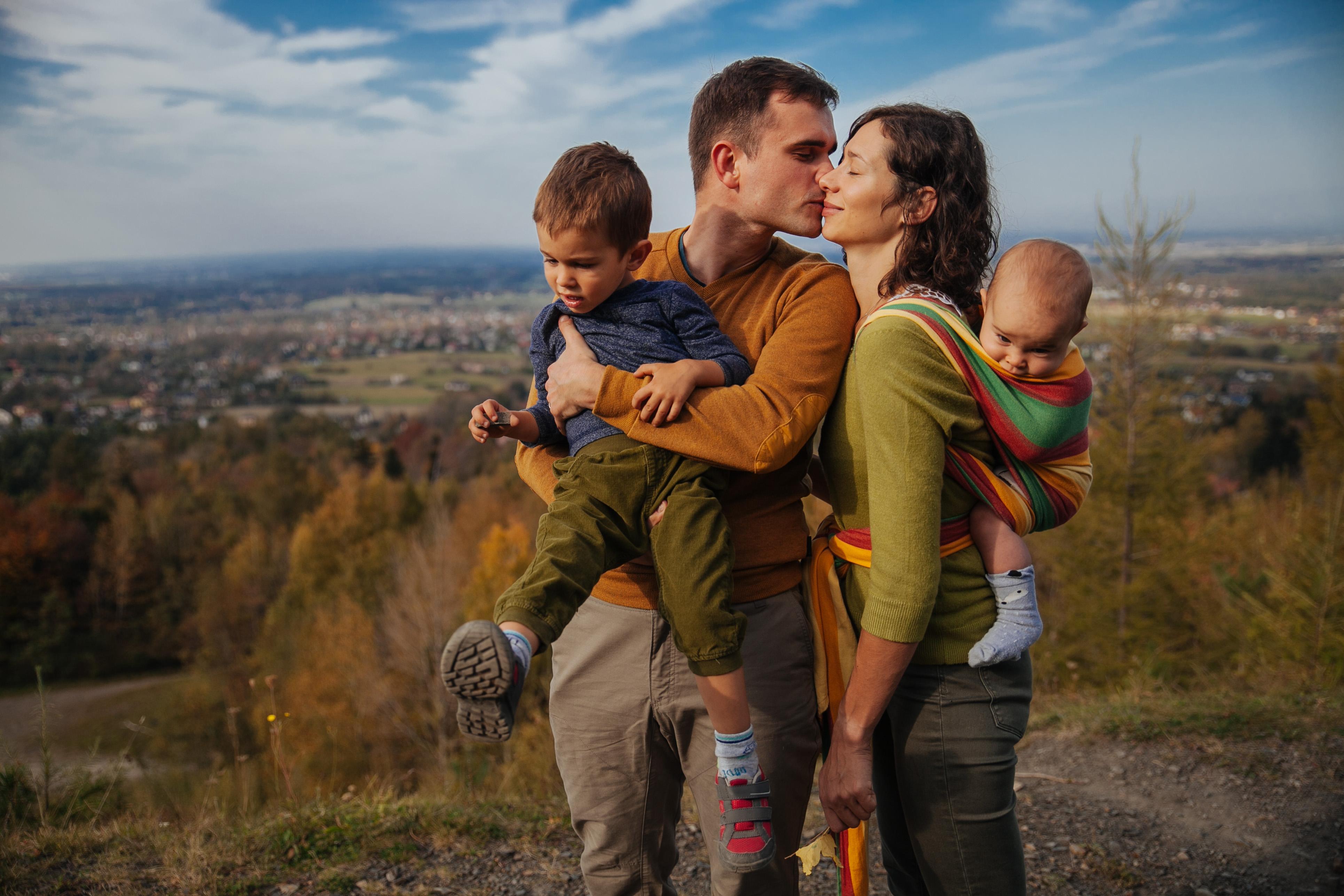 rodzina stoi na górze, lest lekko przytulona, mężczyzna całuje kobietę