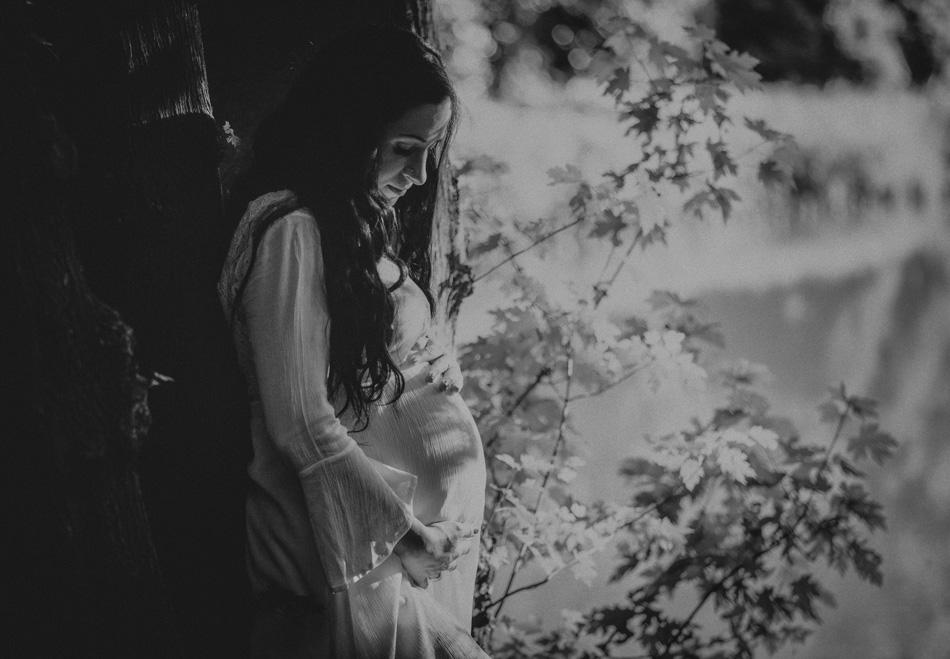 młoda kobieta spogląda na swój ciężarny brzuszek, obejmuje go dłońmi